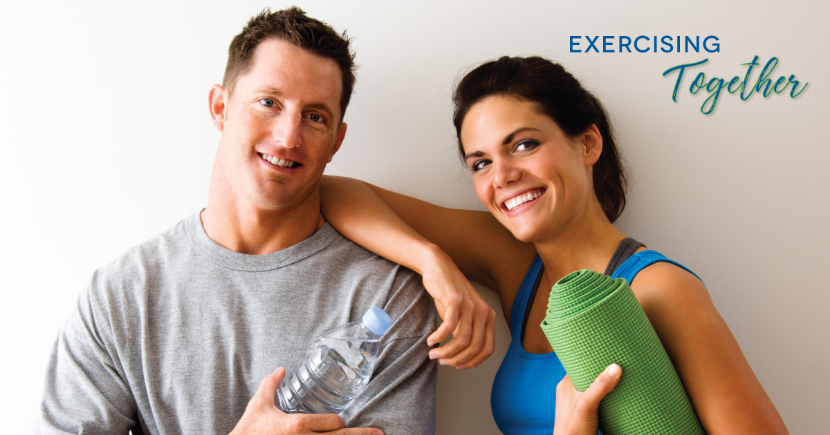 Exercising Together - a man and woman smiling while holding a yoga mat