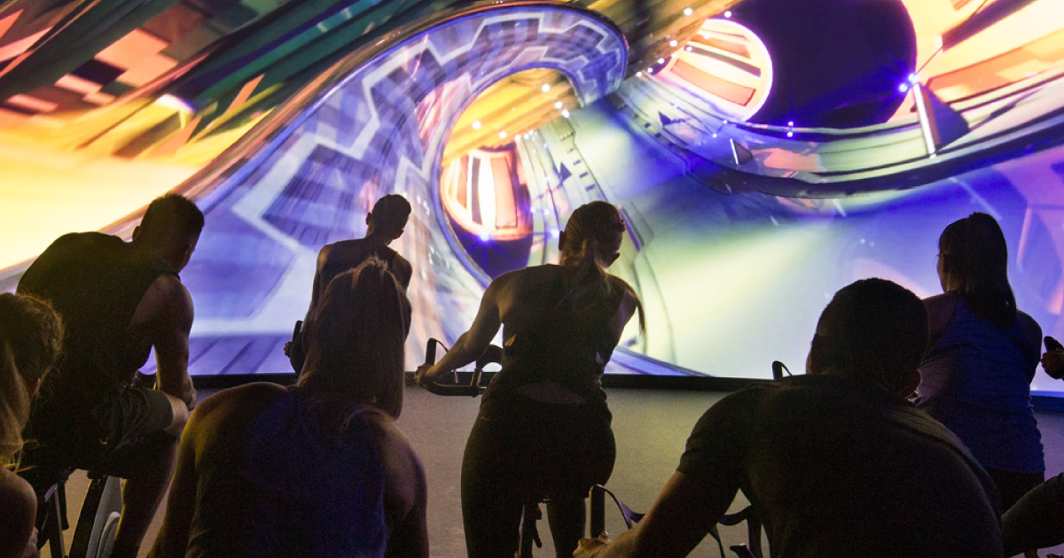 A group of seven people on exercise bikes in front of a screen projecting a rollercoaster