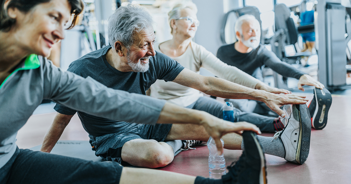 Older People In Gym Stretching Sitting Down